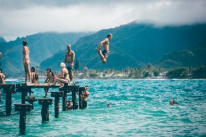 Man with confidence jumping off a pier while a group of people watch