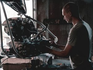 A man from the Australian economy working on a car engine