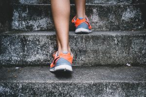 Women in sneakers making slow progression up a set of stairs